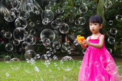Asian Little Chinese Girls Shooting Bubbles from Bubble Blower Stock Image