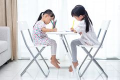 Asian Little Chinese sisters doing homework. At home stock image