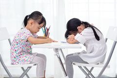 Asian Little Chinese sisters doing homework. At home royalty free stock photos