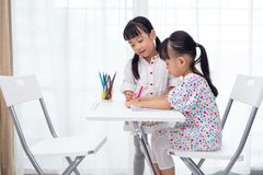 Asian Little Chinese sisters doing homework. At home royalty free stock photography