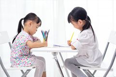 Asian Little Chinese sisters doing homework. At home stock images