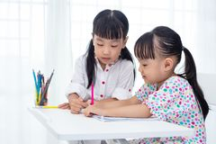 Asian Little Chinese sisters doing homework. At home stock photos