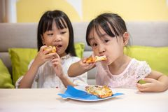 Asian Little Chinese sisters Eating pizza. At restaurant royalty free stock image