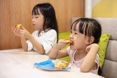 Asian Little Chinese sisters Eating pizza. Asian Little Chinese sisters Eating sisters at restaurant royalty free stock photos