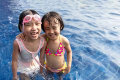 Asian Little Chinese Sisters Playing in Swimming Pool royalty free stock photography
