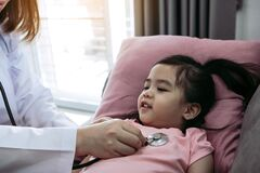Free Asian Little Girl A Woman Slept In A Pillow On The Sofa For A Female Doctor Using Stethoscope On A Heartbeat At Home Stock Photos - 179374053
