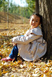 Asian little girl in autumn. Very cute Royalty Free Stock Photos
