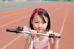 Asian little girl and bicycle Royalty Free Stock Photo