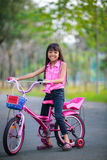 Asian little girl on bicycle in the park Royalty Free Stock Photos