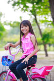 Asian little girl on bicycle in the park Royalty Free Stock Image