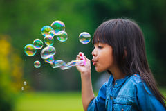 Asian little girl is blowing a soap bubbles. Outdoor Portrait Stock Image