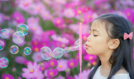 Asian little girl is blowing a soap bubbles. In cosmos garden, Outdoor Portrait Royalty Free Stock Photos