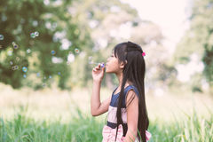 Asian little girl is blowing a soap bubbles in the park Stock Image