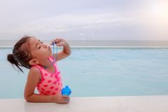 Asian little girl blowing soap bubbles in swimming pool at the s. Easide Stock Photo
