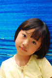 Asian little girl on blue background Royalty Free Stock Photos