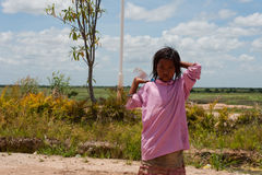 Asian little girl with bottle stands near the road Stock Images