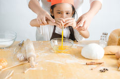 Asian little girl breaking shell of egg Royalty Free Stock Photography
