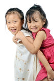 Asian little girl carries her sister on her back Stock Images