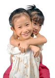 Asian little girl carries her sister on her back Stock Image