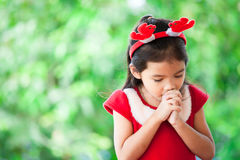 Asian little girl in christmas dress folded her hand in prayer. Cute asian little girl in christmas dress folded her hand in prayer on green nature background Stock Image