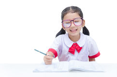 Asian little girl doing homework with smile isolated on white ba Royalty Free Stock Image