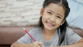 Asian little girl doing homework and smiling with happiness with copy space composition.  stock video footage