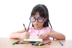 Asian little girl draw on a book Stock Photos