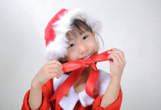 Asian little girl dressed in Santa Claus holding red ribbon Royalty Free Stock Image