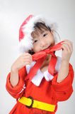 Asian little girl dressed in Santa Claus holding red ribbon Royalty Free Stock Photo