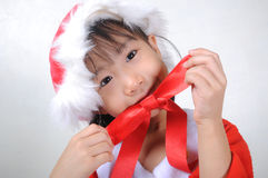 Asian little girl dressed in Santa Claus holding red ribbon Royalty Free Stock Images