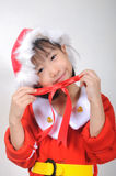 Asian little girl dressed in Santa Claus holding red ribbon Stock Images