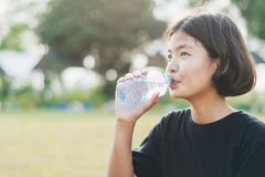 Asian little girl drinking fresh water from plastic bottle with. Sunset background Stock Images