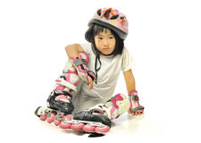 Asian little girl feel bored while fall down in roller skates. stock images