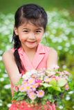 Asian little girl with flower. In field of flowers Stock Image