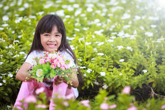 Asian little girl with flower in field of flowers Royalty Free Stock Photo