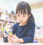 Asian little girl is focusing on painting art doll. Asian little girl is focusing on painting her art doll Stock Photo