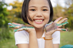 Girl with hands painted in colorful paints Stock Images