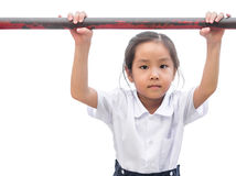 Asian  little girl hanging on old horizontal bar Stock Images