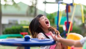 Asian little girl having fun playing on carousel stock photo