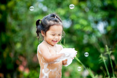 Asian little girl having fun to play with water Royalty Free Stock Images