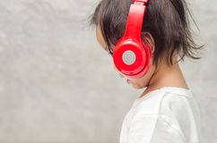 Asian little girl with headphones in the bedroom at home Stock Images