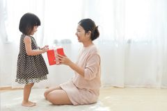 Asian Little girl and her Mother holding a red gift box together. In a white room for Birthday, Christmas and New year. Copy space. Happy Family celebration Royalty Free Stock Photography