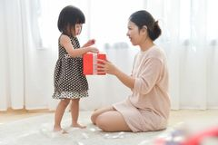 Asian Little girl and her Mother unwrapping a red gift box toget. Her in a white room for Birthday, Christmas and New year. Copy space. Happy Family celebration Royalty Free Stock Image