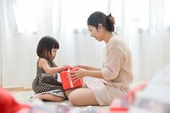 Asian Little girl and her Mother unwrapping a red gift box toget Royalty Free Stock Photo