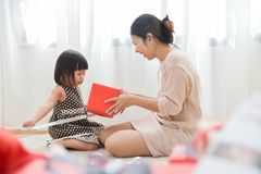 Asian Little girl and her Mother unwrapping a red gift box toget Stock Photos