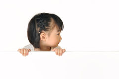 Asian little girl hiding behind white board Stock Image