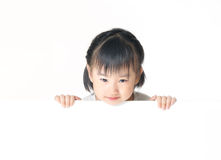 Asian little girl hiding behind white board Stock Photo
