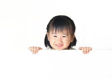 Asian little girl hiding behind white board Royalty Free Stock Images