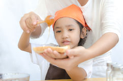 Asian little girl hold the bread and honey dipper stick with mot Royalty Free Stock Photo