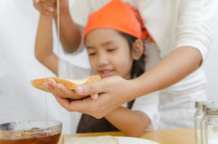 Asian little girl hold the bread and honey dipper stick with mot Royalty Free Stock Photos